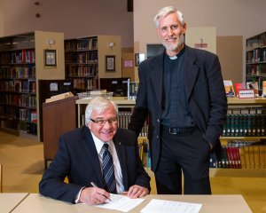 Board Chairman Rev. Robert Krestick and President Thomas Winger sign the agreement